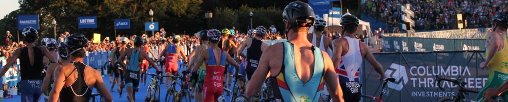 Men running into transition with bikes at World Triathlon Championships